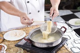 stock photo of noodles  - Chef holding colander with cooked Noodle  - JPG