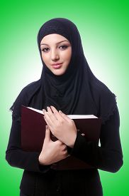 picture of burka  - Young muslim woman with book on white - JPG
