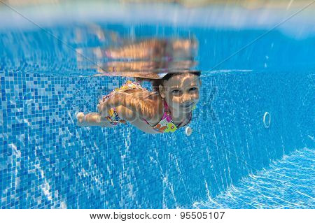 Happy active child swims underwater in pool, beautiful healthy girl swimming and having fun