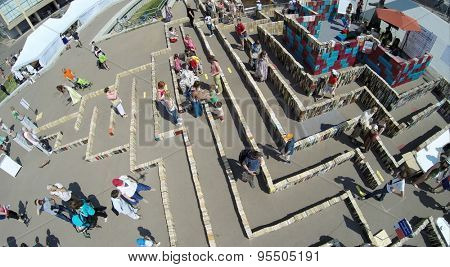 RUSSIA, MOSCOW - MAY 24, 2014: People walk by maze of books on territory of All Russia Exhibition Center at spring sunny day. Aerial view