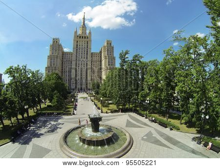 RUSSIA, MOSCOW - MAY 23, 2014: Citizens walk by square with round fountain near tall residential house on Kudrinskaya street at sunny spring day. Aerial view