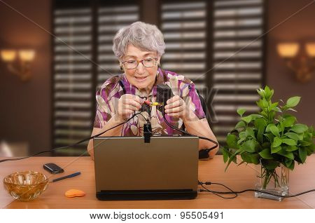 Old woman is sitting at desk with audio video adapter