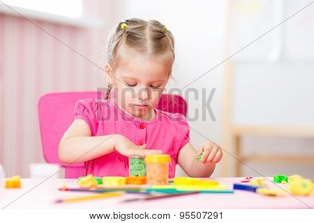 child girl doing crafts at nursery or day care center