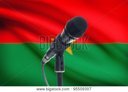 Microphone On Stand With National Flag On Background - Burkina Faso
