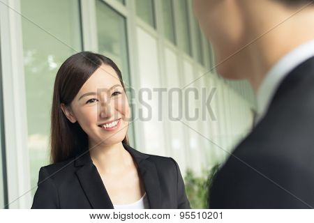 Asian business woman talk to others in the city.