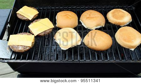 Hamburger patties with processed cheese slices cooking on an outdoor table top barbecue.  Buns toast