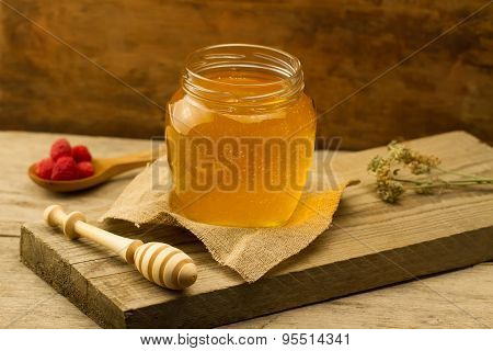 Glass Jar Of Honey With Drizzler, Raspberries, Jute Fabric, Dried Flowers On Wooden Background