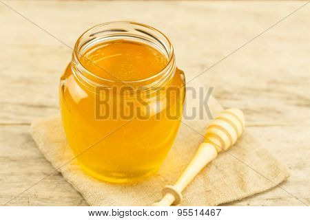Glass Jar Of Honey On Jute Fabric With Drizzler On Wooden Background