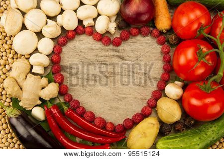 Vegetables In The Shape Of A Heart On Wooden Background, Vegetarian Food. A Healthy Diet