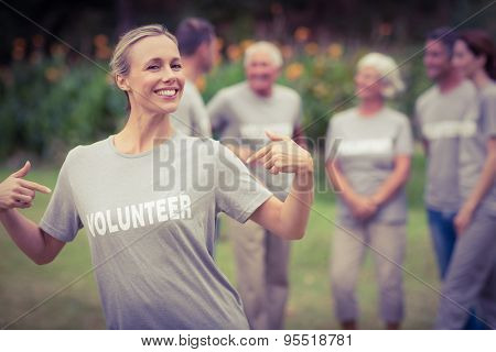 Happy volunteer showing her t-shirt to camera on a sunny day