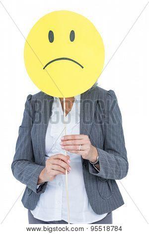 Businesswoman holding sad smiley face on white background