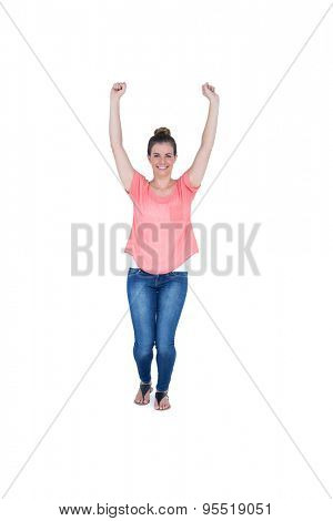 Happy pretty casual brunette cheering in front of camera on white background