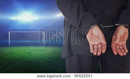 Businessman in handcuffs against football pitch with bright lights