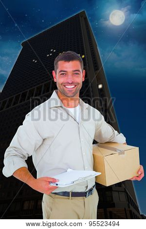 Delivery man with cardboard box and clipboard on white background against city at night