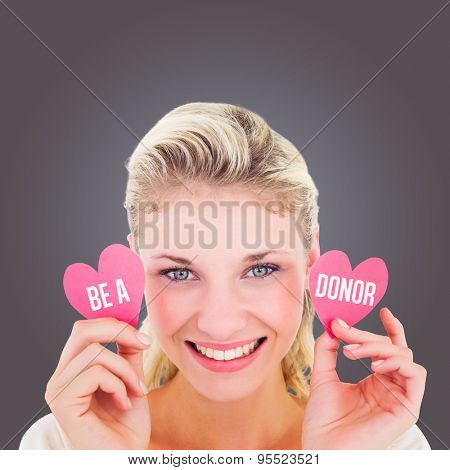Attractive young blonde holding little hearts against grey vignette