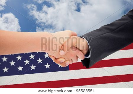 Close up of a handshake against bright blue sky with clouds