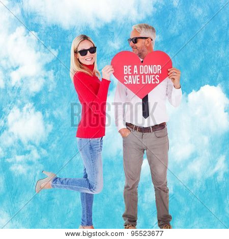Cool couple holding a red heart together against painted blue sky