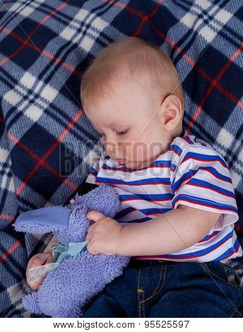 Little boy plaing with plush toy