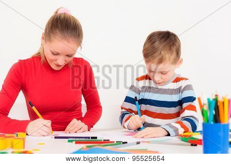 Son drawing with mother at table