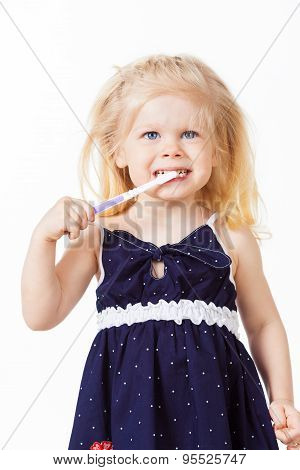 Beautiful blonde haired baby girl brushes her teeth