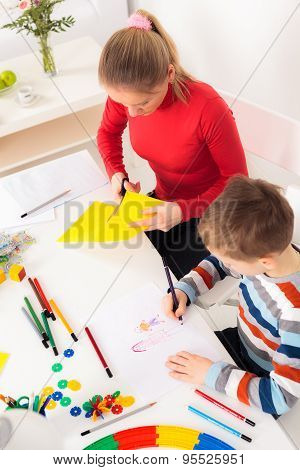 Little boy drawing picture and his mother cutting paper