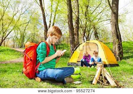 Boy with red backpack writes notebook at camping