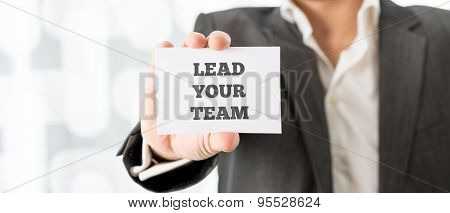 Business Executive Holding Up A White Card With A Lead Your Team Sign