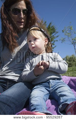 Baby And Mother Eating In Park