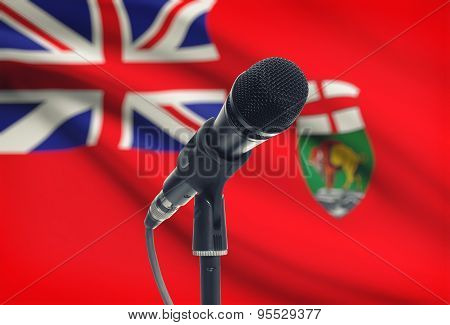 Microphone On Stand With Canadian Province Flag On Background - Manitoba