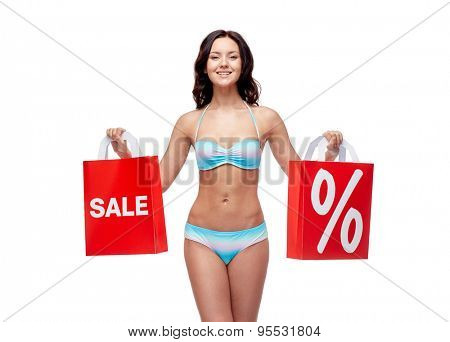 people, fashion, swimwear, summer sale and beach concept - happy young woman in bikini swimsuit with red shopping bags