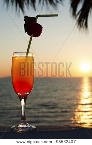 Glass With Cocktail And A Straw Against Blue Sea, Sky And Sunset