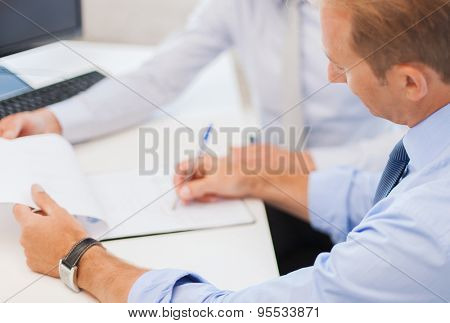 businesss and office concept - businessmen with notebook discussing graphs on meeting