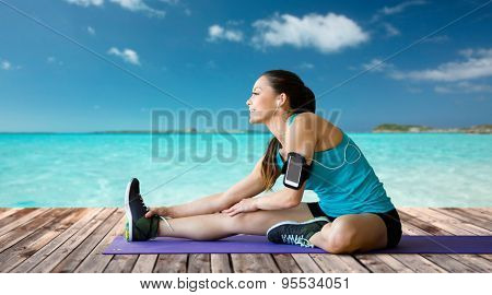 fitness, sport, training, technology and people concept - smiling woman with smartphone and earphones listening to music and stretching on exercise mat over sea and wooden berth at resort background