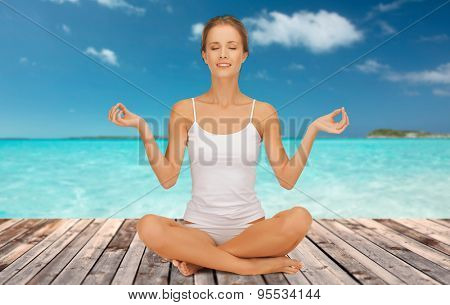 people, health, wellness and meditation concept - woman in underwear meditating in yoga lotus pose on wooden floor over sea and blue sky background