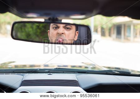 Guy Sticking Tongue Out In Rearview Mirror