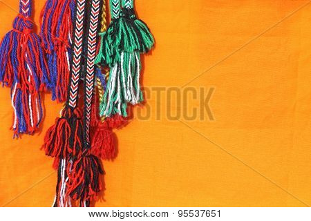 Colorful Tassels Of A Hippie Belts On Orange Background.