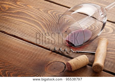 Wine glass, cork and corkscrew over wooden table with copy space