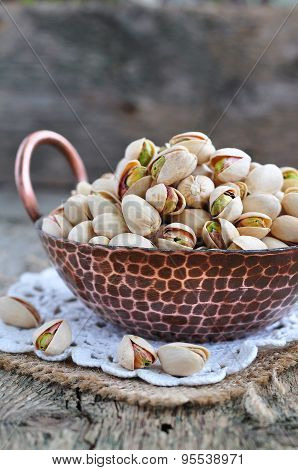 Pistachio in a copper plate on a wooden table