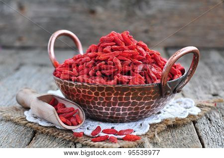 Dried goji berries in a copper plate on a wooden table