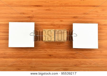 Two Paper Notes With Holders In Different Directions On Wood