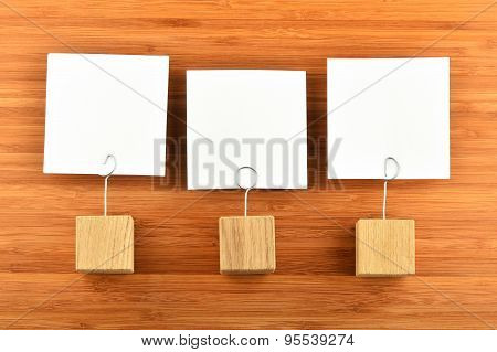 Three Paper Notes With Holders On Wooden Background