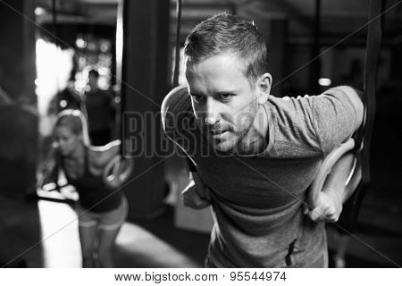 Black And White Shot Of Man Exercising With Gymnastic Rings