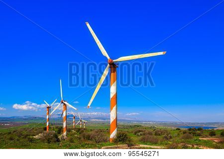 Israel. Several huge modern windmills. Seen in the distance the snow-covered Hermon. Flowering Golan Heights on a sunny day
