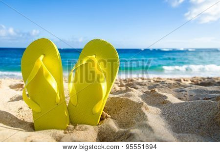 Yellow Flip Flops On The Sandy Beach
