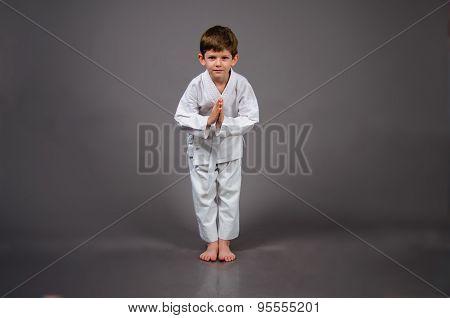 Karate boy in white kimono studio