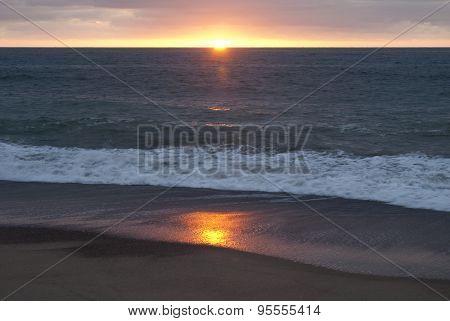 Setting Sun On An Ocean Shore