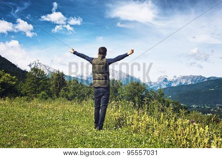 Man rejoicing with his arms outstretched as he stands on a plateau overlooking the Alps in the Berchtesgaden National Park, Germany