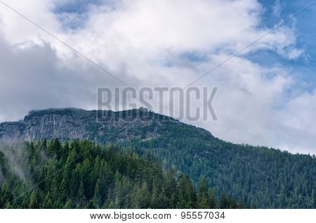 Rocky mountain outcrop beneath cloudy sky, expanse of mist-covered fir trees in foreground