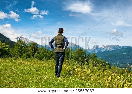 Rear view of a male tourist standing on a grassy plateau enjoying the scenic Bavarian alps in the Berchtesgaden National Park