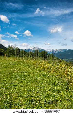 Green grassy plateau in the Berchtesgaden Alps in Bavaria, Germany overlooking alpine peaks with a smattering of snow